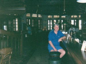 John in the Long Bar at Raffles Hotel, lining up for a Gin sling and peanuts