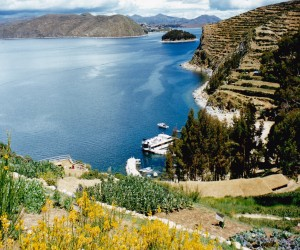From Sun Island tiers of Andean flora and vegetables and grain looking back at our catamaran on Lake Titicaca