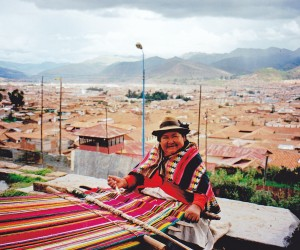 Peruvian lady weaving a mat overlooking Cuzco's red rooftops